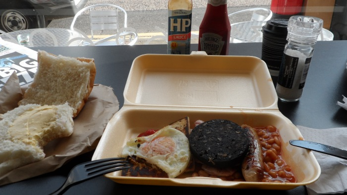 Breakfast from a local cafe. A bun, tatties, black pudding, baked beans, sausages, bacon and HP brown sauce. Oh, and a mug of workmans' tea.