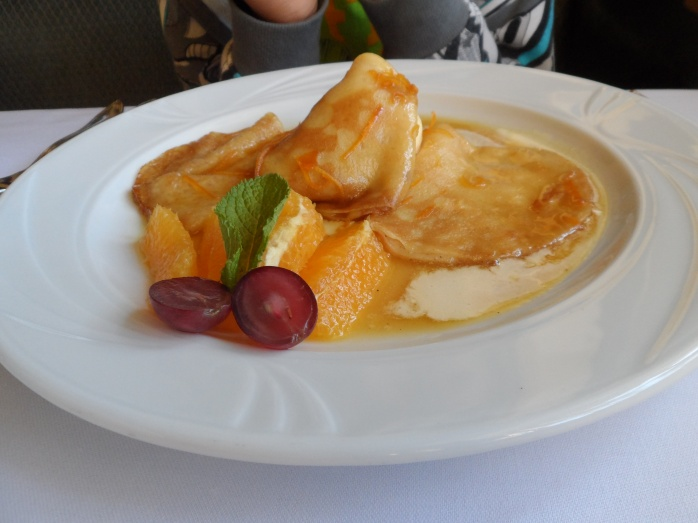 Crêpes Suzette – in orange liqueur served with vanilla ice–cream and fruit.