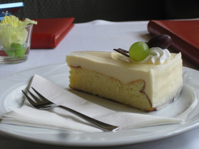 Real cake with custard icing and a single green and red grape with a swirl of cream and a sliver of chocolate!
