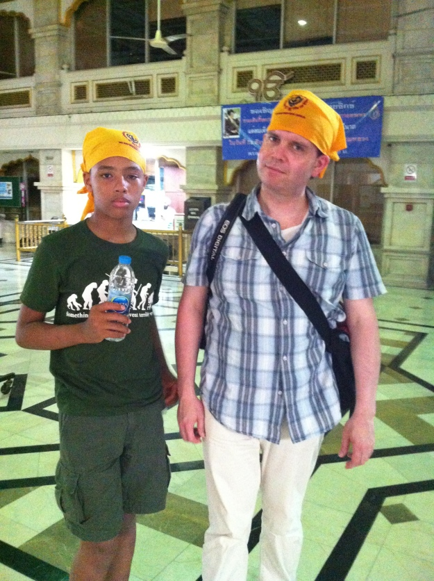 """The Music Producer and """"The Tall Young Gentleman"""" donning bright yellow scarves at the Sikh temple in Bangkok, Thailand."""