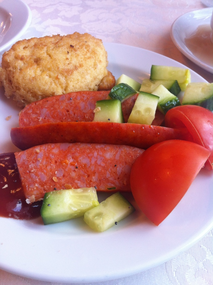 """We had a """"healthier"""" Czech breakfast of sort of scrambed egg pancake ball, some Czech sausage, cucumbers, tomatoes, and some ketchup!"""
