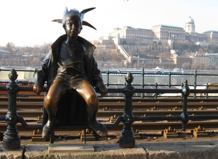 The Little Princess (Kiskirálylány) statue sitting on the railings of the Danube promenade in Budapest, Hungary.