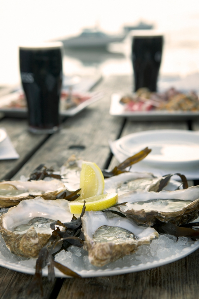 Oysters and stout on a wooden table outside a pub, England UK - ©VisitBritain Daniel Bosworth