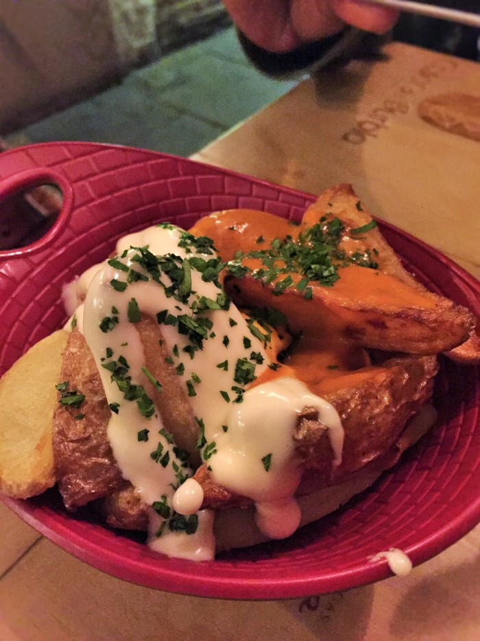 Spanish patatas bravas - baked potato wedges with their skins on and sour cream and spicy sauce.