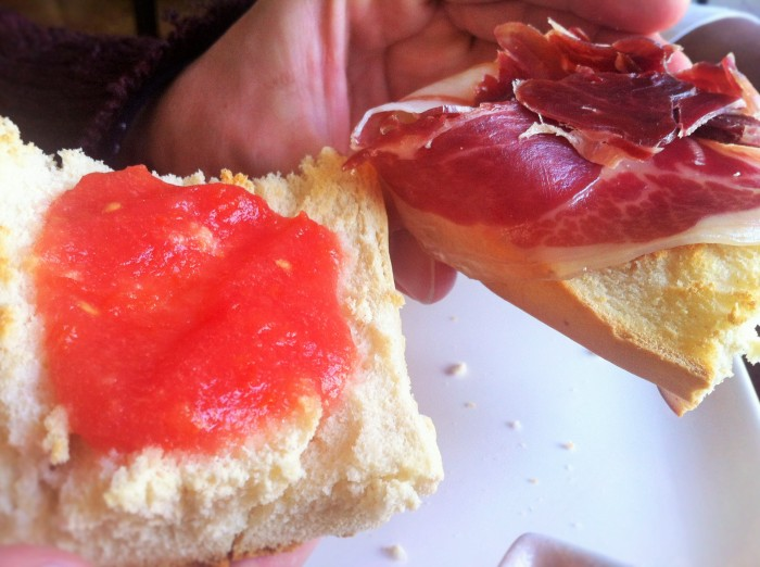 A local Spanish baguette sandwich filled with slices of Serrano or Iberian ham accompanied by very, very squashed and sqeezed tomatoes!