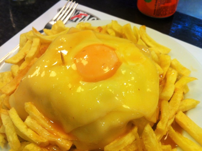 Francesinha, otherwise known as Little Frenchie! A Porto-derived traditional Portuguese sandwich made from a triple-decker mass of bread, ham, chouriço and roast meat, covered with masses of melted cheese, a fried egg on top, and served on a large plate of hot chips, with some sort of sauce!