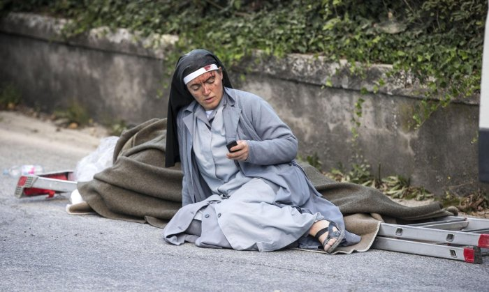 A nun checks her mobile phone as she lies near an earthquake victim in Amatrice, Italy. ©Massimo Percossi / AP