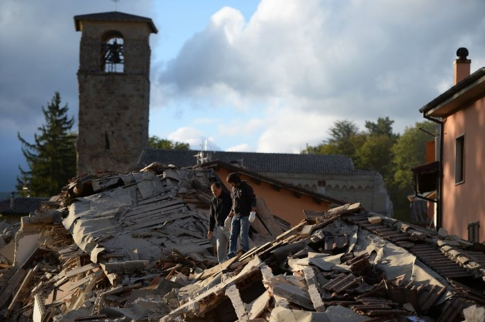 Two men walk on a flattened house in Amatrice, Italy. ©Filippo Monteforte / AF / Getty Images