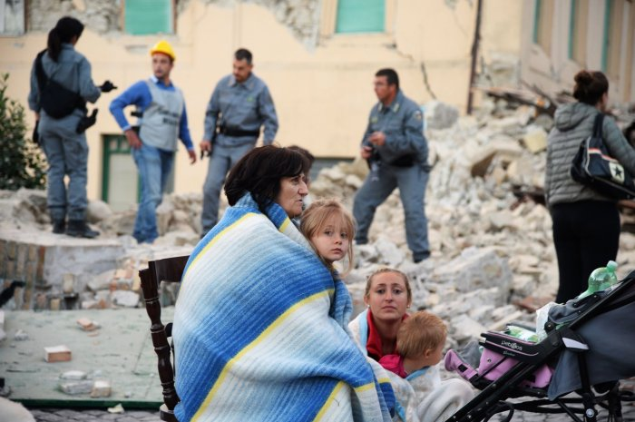 Victims sit among the rubble of a house in Amatrice, Italy. ©Filippo Monteforte / AFP / Getty Images