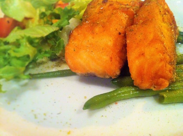 Grilled salmon with green beans, lemon slices, and a side salad.