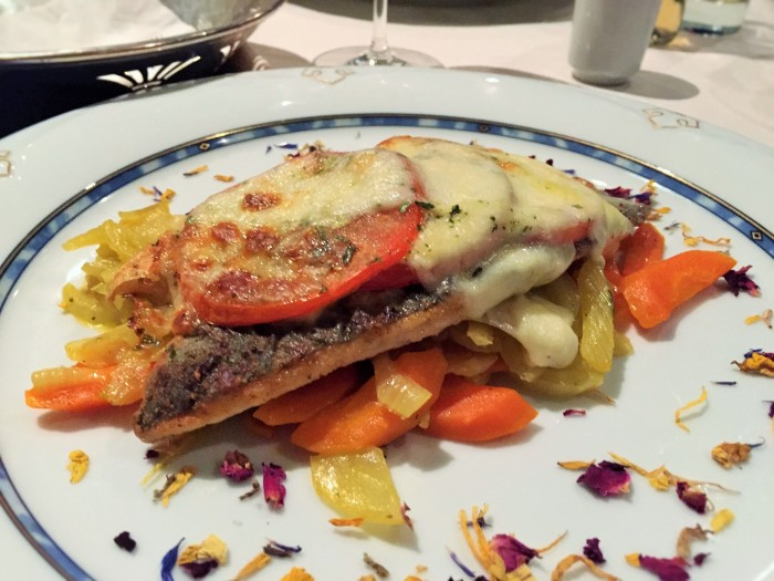 Magnificent grilled fish over saute vegetables, covered in tomato and a cheese sauce, sprinkled with edible flowers! ©The Music Producer - Frank Böster