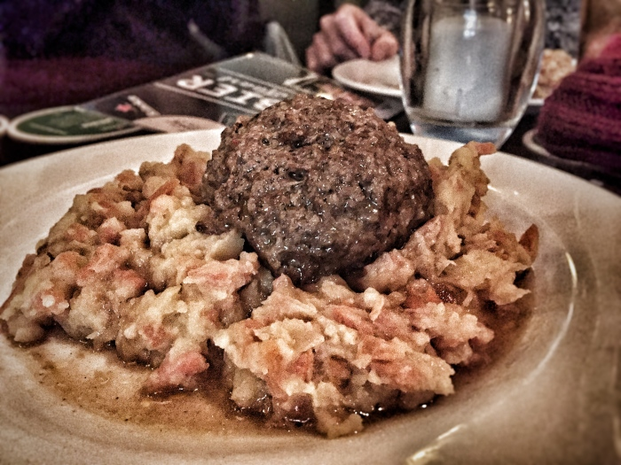 A huge meatball with stamppot, otherwise known as a Dutch traditional meal of mashed potatoes and several vegetables, or fruit!
